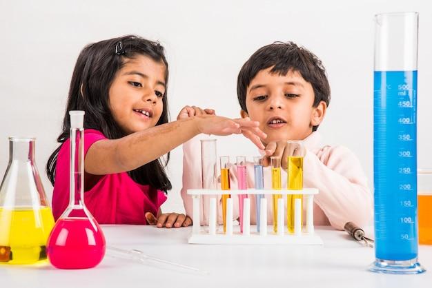 Curieux petits écoliers indiens ou scientifiques étudiant la science, expérimentant des produits chimiques ou un microscope en laboratoire, mise au point sélective