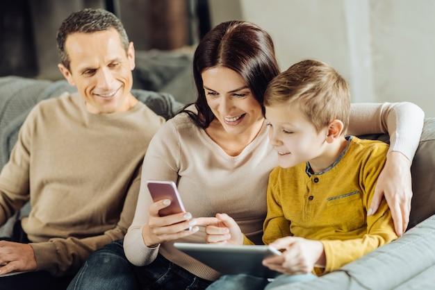 Curiosité enfantine. agréable petit garçon câlins avec sa mère et lui posant des questions sur le jeu sur son téléphone pendant que son père les regarde avec curiosité