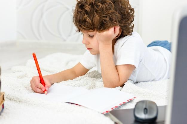 Curly boy est engagé à l'ordinateur. écolier attrape sa tête avec surprise. concept de difficultés d'enseignement à domicile, à distance.