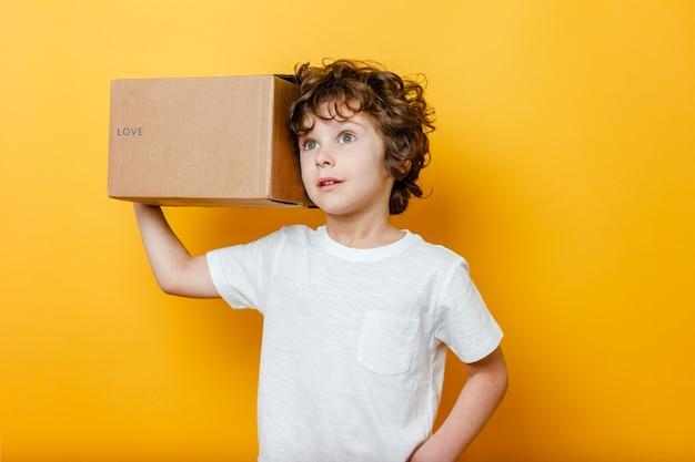 Curly boy tient une boîte en carton avec le titre love sur son épaule sur jaune