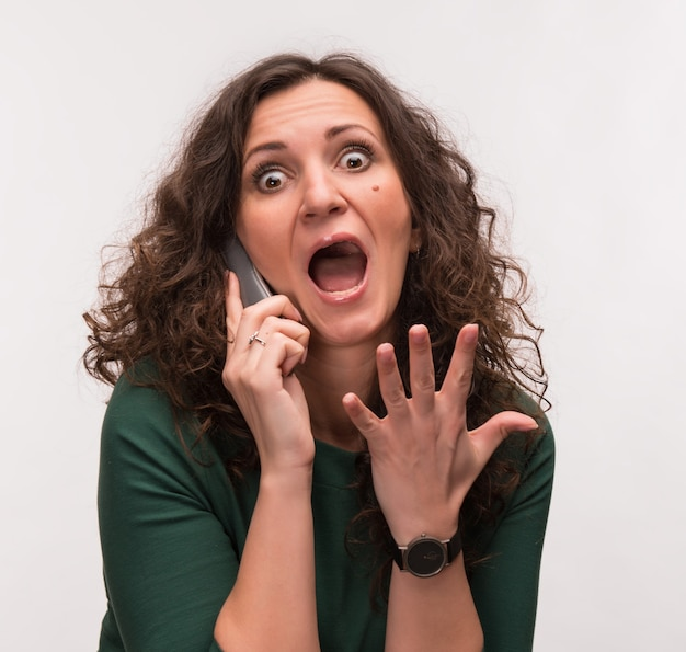 Curly brunette choqué parlant au téléphone sur un fond gris