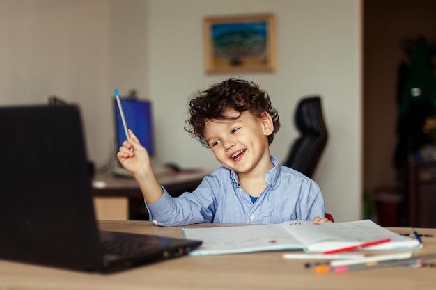 Curly cute boy at home formation en ligne un enfant d'âge préscolaire sur un ordinateur portable apprend et écrit dans un cahier une tâche