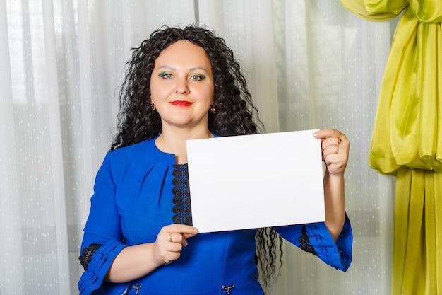 Curly femme brune joyeuse tenant une plaque d'espace copie dans ses mains. photo horizontale