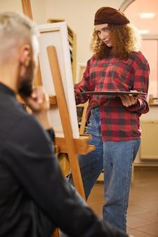 Curly girl dessine et regarde un homme assis devant elle