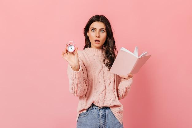 Curly girl avec étonnement se penche sur la caméra sur fond rose. femme en pull tenant livre et réveil.