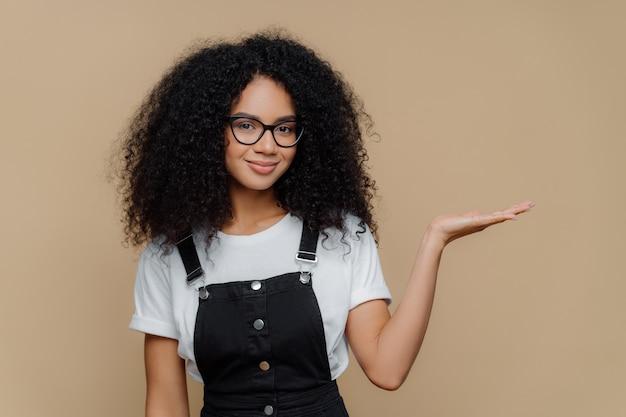 Curly girl lève la paume, détient un espace vide, porte des lunettes transparentes