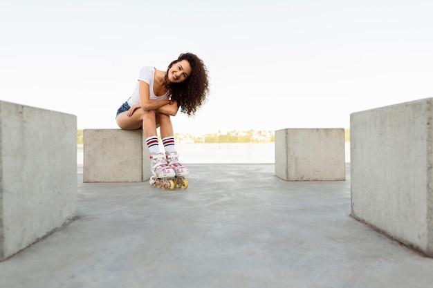 Curly girl posant tout en portant des rollers avec espace copie