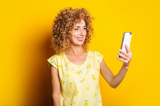 Curly happy young woman talking on video chat sur le téléphone sur une surface jaune