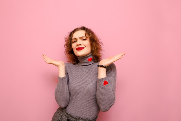 Curly hipster girl en pull gris écarte les bras