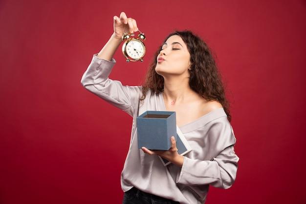 Curly jeune femme regardant l'horloge.