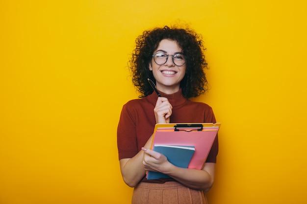 Curly jeune fille caucasienne portant des lunettes tient un stylo et quelques livres posant sur un fond jaune