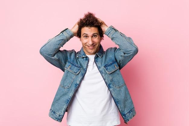 Curly mature man wearing a denim jacket on pink background rit joyeusement en gardant les mains sur la tête.