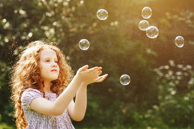 Curly petite fille attraper un bulles de savon.