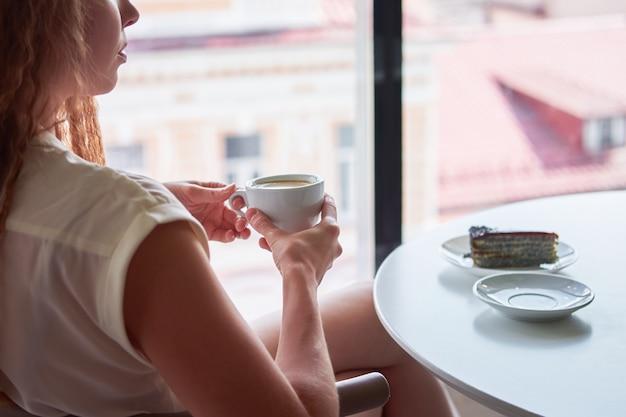 Curly rousse maigre femme assise dans un café en face de la fenêtre avec une tasse de café et en observant le paysage urbain européen