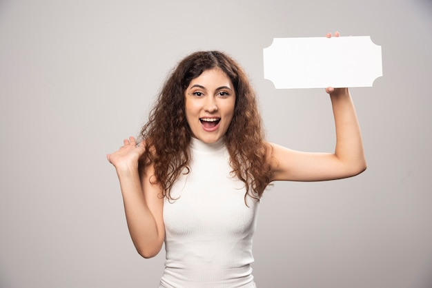 Curly woman holding white paper en riant