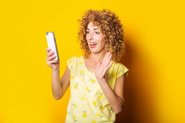 Curly young woman talking on video chat sur le téléphone sur une surface jaune