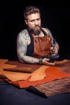 Currier de cuir produisant des pièces en cuir sur son lieu de travail.