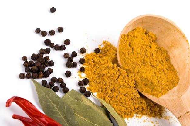 Curry sur une cuillère en bois, poivre, piment et feuilles de laurier sur fond blanc