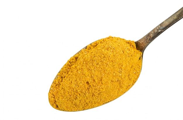 Curry dans une vieille cuillère sur un fond blanc.
