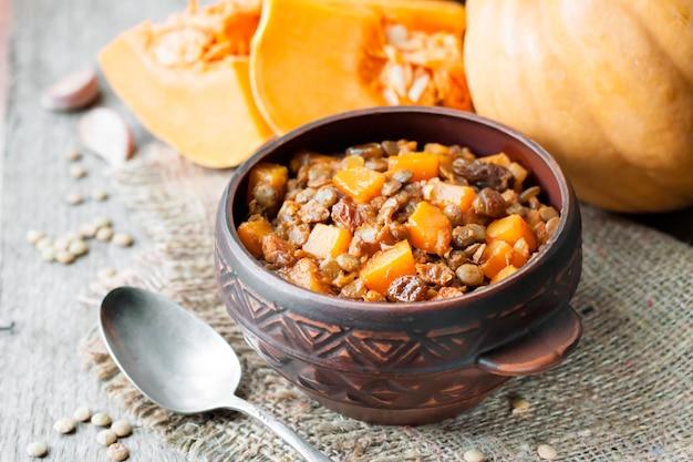 Curry épicé maison avec lentilles vertes, citrouille et raisins secs dans un bol en céramique rustique