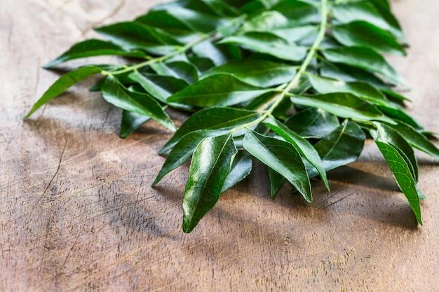 Curry feuilles fraîches sur le dessus vue de fond en bois avec copie espace