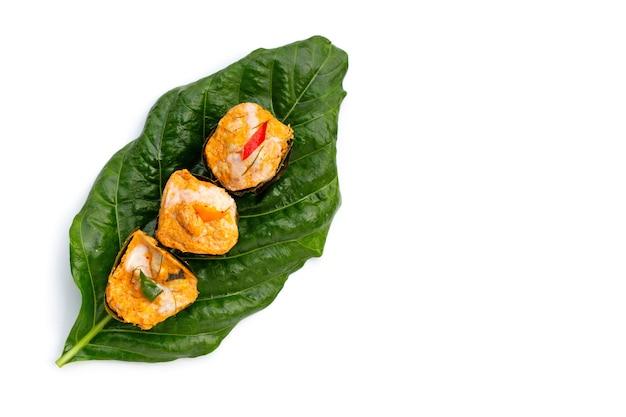 Curry de poisson en flux thaïlandais en feuilles de bananier sur feuille de noni ou morinda citrifolia sur fond blanc.