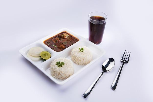 Curry de poisson indien et riz servis dans une assiette carrée blanche sur fond coloré . servi avec une boisson fraîche