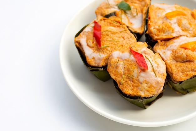 Curry de poisson en streaming thaïlandais dans des feuilles de bananier sur une plaque blanche