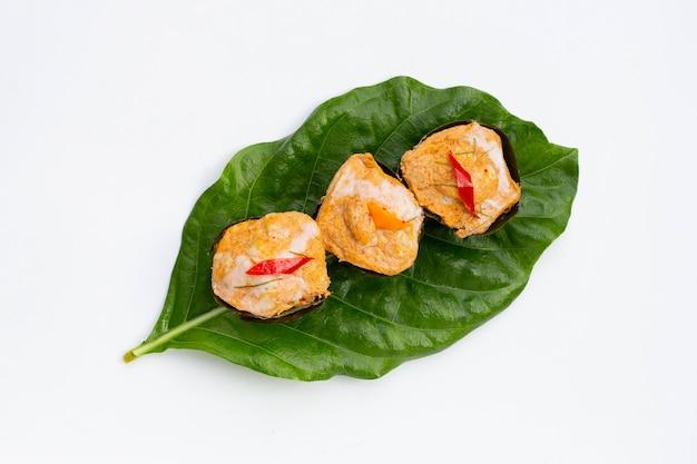 Curry de poisson thaï dans des feuilles de bananier sur des feuilles de noni ou de morinda citrifolia sur une surface blanche.