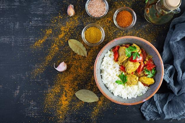 Curry de poulet épicé avec du riz. sauce au curry avec poulet et riz sur fond sombre. vue de dessus