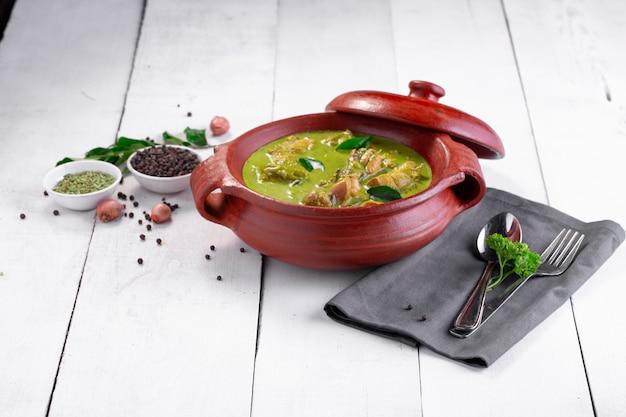 Curry de poulet vert avec des ingrédients crus qui est disposé dans un pot en terre cuite
