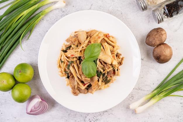 Curry de pousses de bambou, ajoutez le porc dans un plat blanc.