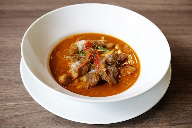 Curry rouge avec une côte de porc sur une table en bois