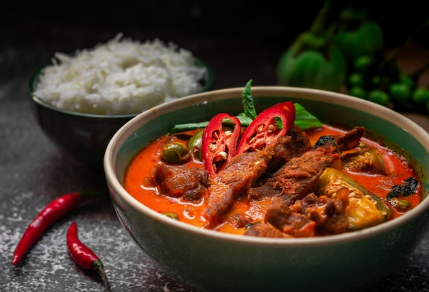 Curry thaï épicé avec de la viande de porc servant avec du riz et la décoration avec des ingrédients végétaux à base de plantes comme le piment et l'aubergine sur fond rustique - cuisine thaïlandaise