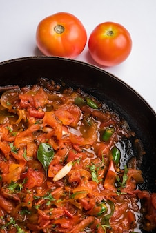 Curry de tomates ou sabzi également connu sous le nom de sabji ou chutney servi dans un bol, menu de légumes indien populaire pour le plat principal. mise au point sélective