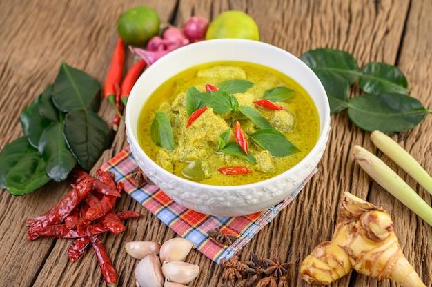 Curry vert dans un bol avec citron vert, oignon rouge, citronnelle, ail et feuilles de lime kaffir
