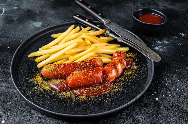 Currywurst allemand traditionnel, servi avec des frites. table noire. vue de dessus.