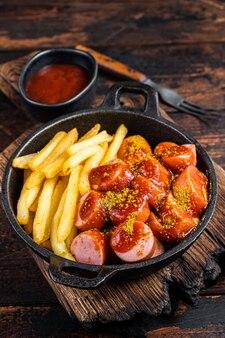 Currywurst street food repas, épices au curry sur wursts servi des frites dans une poêle