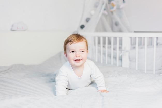 Cute blonde bébé dans un lit blanc