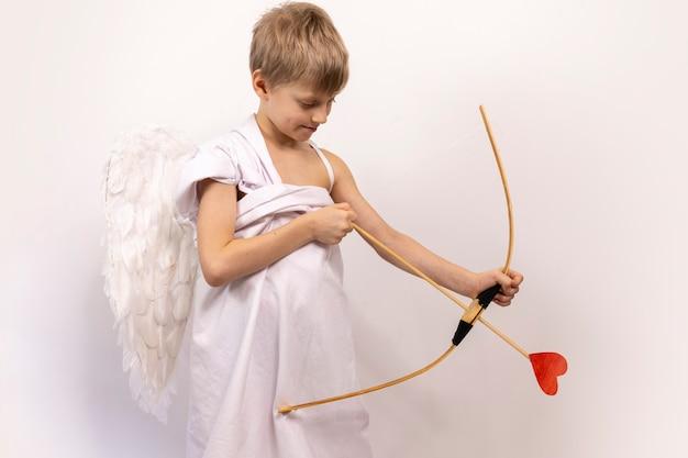 Cute boy cupid vise les amateurs d'arc et de flèche. ange dans le ciel félicite pour la saint-valentin