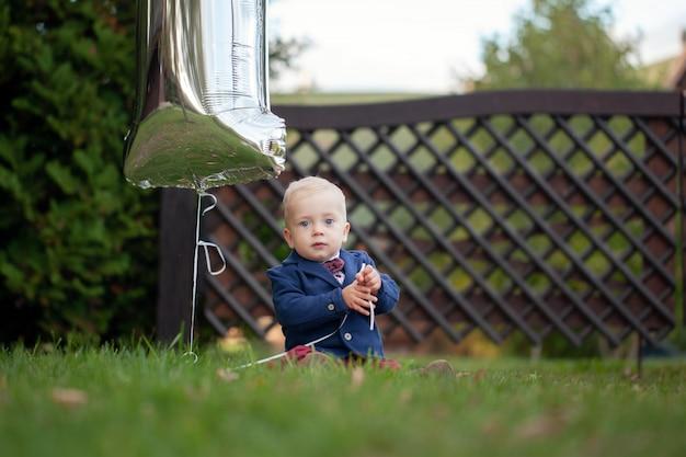 Cute espiègle sourit blond. garçon de 1 ans assis sur une pelouse verte en été.