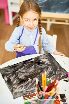 Cute girl painting halloween pictures in art class