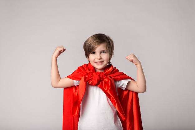 Cute kid superwoman en cape rouge montre son muscle