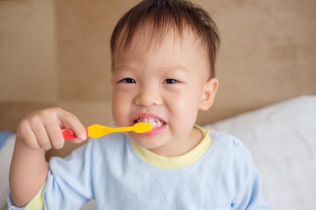 Cute smiling little asian 30 mois / 2 ans enfant garçon enfant portant un pyjama assis dans son lit tenant une brosse à dents et apprendre à se brosser les dents le matin à la maison, soins dentaires pour les enfants concept