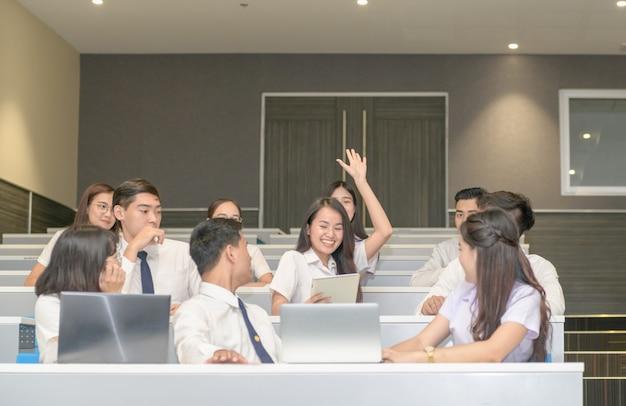 Cute teen student lève les mains pour demander au professeur