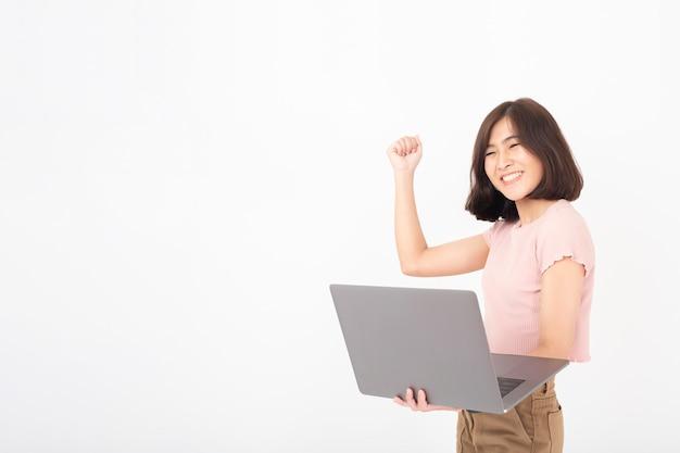 Cute teen teen asiatique travaille avec ordinateur sur mur blanc