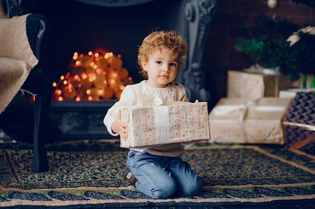 Cutte petit garçon à la maison près de décorations de noël