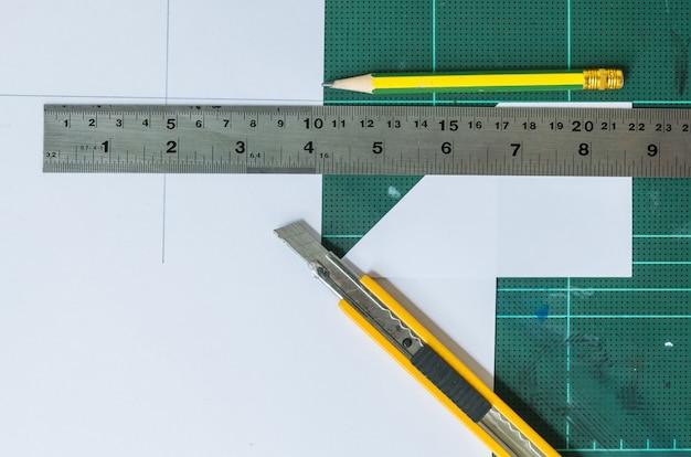 Cutter, crayon de bois et règle sur le vieux fond de tampon en caoutchouc vert