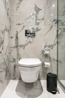 Cuvette de toilette près de la cabine de douche à l'intérieur de la salle de bains moderne