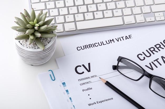 Cv, curriculum vitae avec clavier sur un bureau blanc